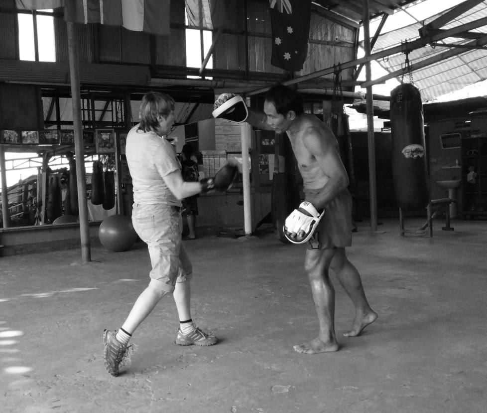 Anne Quinlan hitting Pads with Nook - Lanna Muay Thai black and white